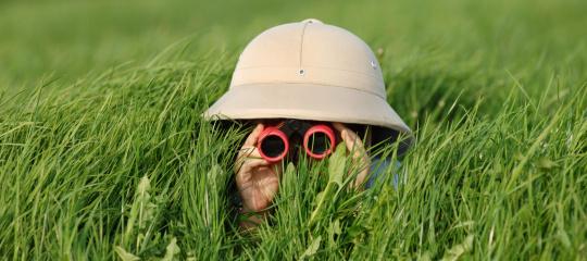 Kind met verrekijker in het gras.jpg